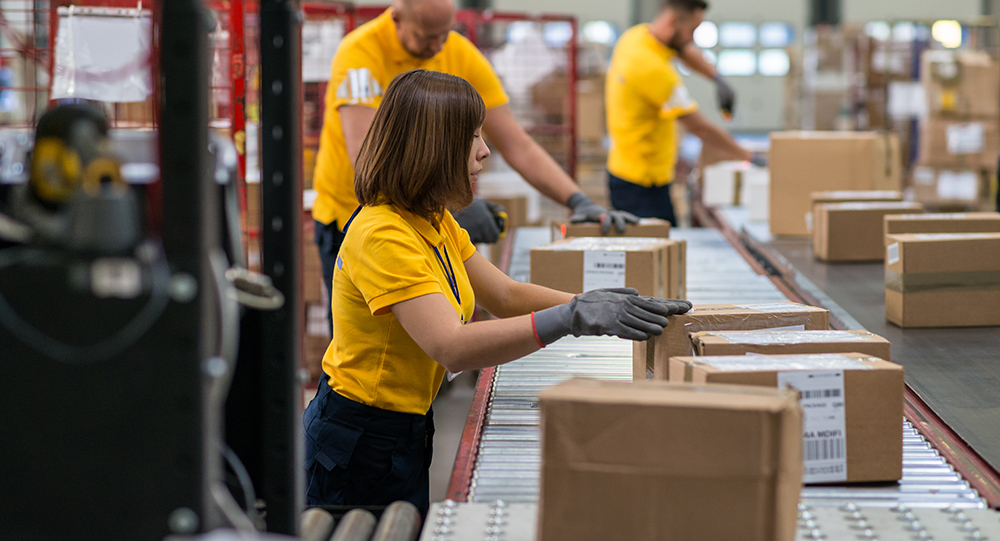Staff lifting and moving boxes off assembly line