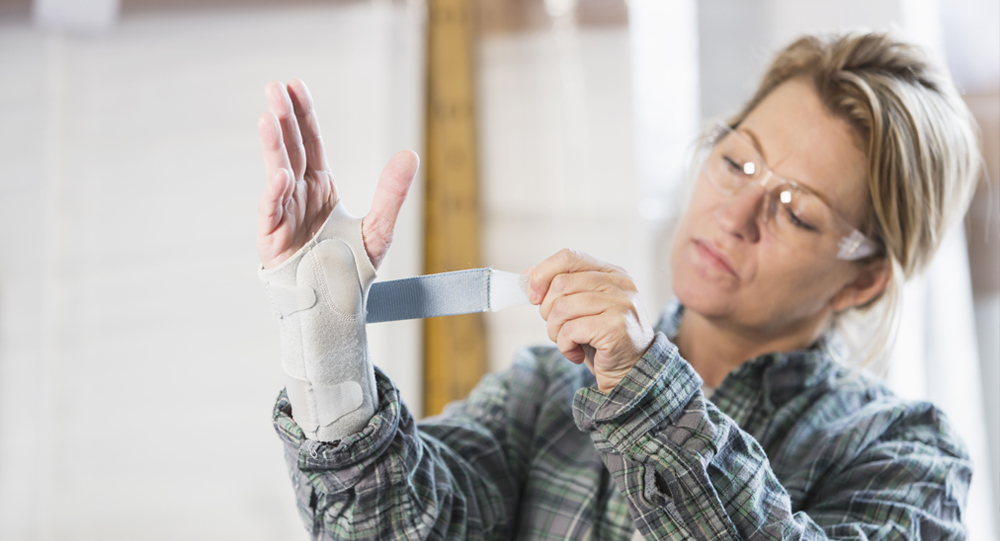 Female warehouse employee wrapping splint around her wrist