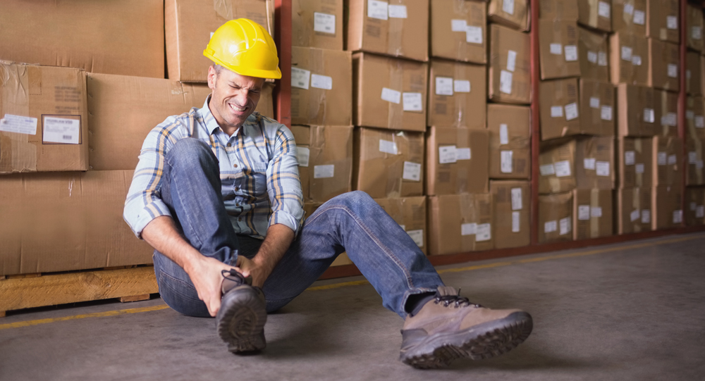 Injured employee holding ankle while sitting on ground